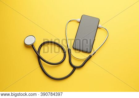 Smartphone And Stethoscope On Yellow Background. Online Medicine (telemedicine) Technology. Service