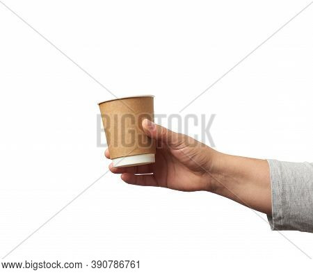 Female Hand Holds Paper Brown Disposable Cup For Coffee And Tea, Part Of Body Isolated On White Back