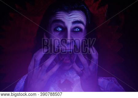 Bloodthirsty vampire bared his teeth in the night in an old medieval castle. Traditional vampire man. Halloween.