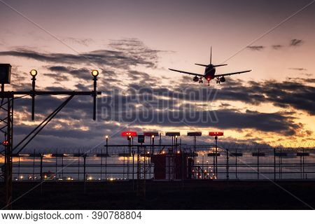 Landing Plane And Dowsing Bird Scarers At The Airport Against The Backdrop Of A Beautiful Pink Sunse