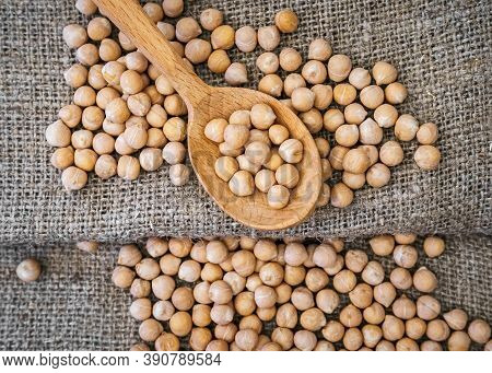 Chickpeas In A Wooden Spoon On A Gray Linen Fabric. Raw Chickpea
