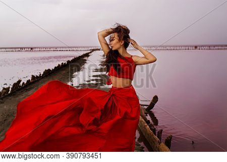 Beautiful Woman On A Pink Lake In A Red Evening Dress