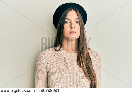 Young brunette woman wearing french look with beret relaxed with serious expression on face. simple and natural looking at the camera.