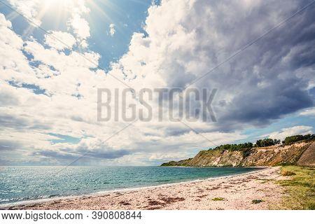 Beach With Cliffs On A Scandinavian Seashore In The Summer. Sun Shining Through The Clouds Over A Da