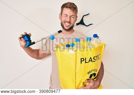 Young caucasian man holding recycling bag with plastic bottles and waste picker winking looking at the camera with sexy expression, cheerful and happy face.