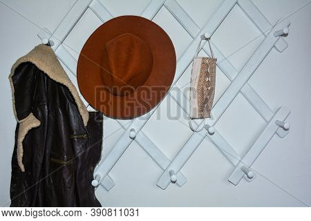 White Hallway Cloakroom With A Suspended Respiratory Protective Mask And With A Hat And Leather Jack