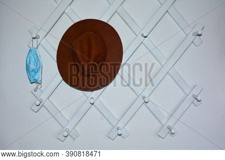White Hallway Cloakroom With A Hung Respirator And A Brown Hat On The Left