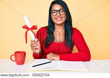 Beautiful latin young woman with long hair holding graduate degree diploma looking positive and happy standing and smiling with a confident smile showing teeth