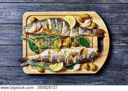 Whole Roasted Seabass Fish With Lemon Wedges And Herbs: Rosemary, Parsley, And Bay Leaf, Served On A