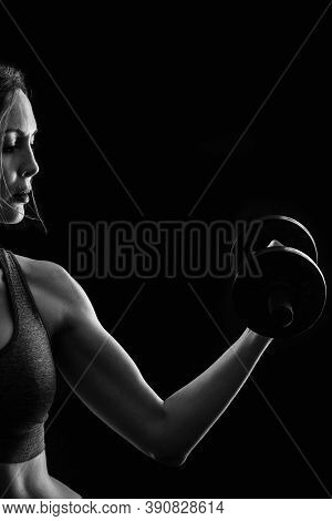 Slim Athletic Woman Holding Dumbbell In The Hand On Black