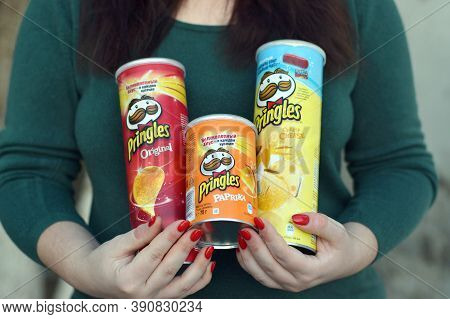 Young Girl Holds Few Pringles Potato Chips Cylinder Packs. Pringles Is A Brand Of Potato Snack Chips