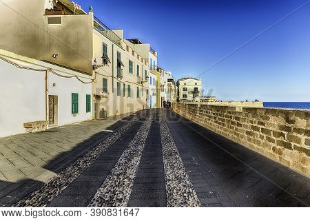 Walking At Sunset On The Historic Ramparts, One Of The Main Sightseeing In Alghero, Famous Center An