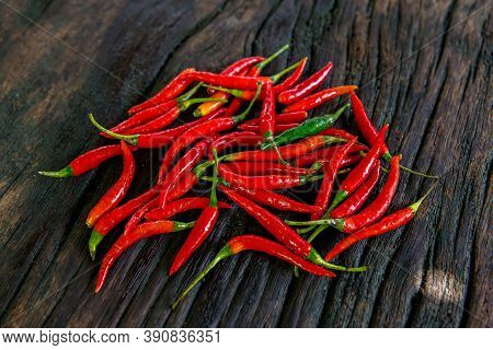 A Group Of Red Peppers On A Wooden Plate