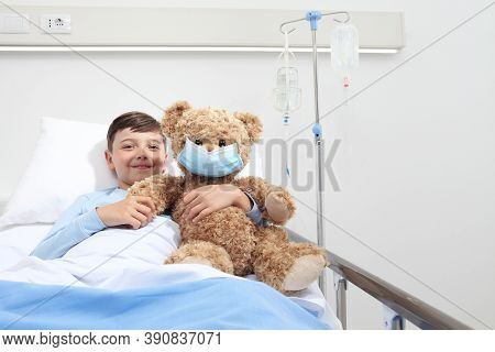 Smiling Child In Hospital Bed With Teddy Bear Wearing Protective Mask, Corona Virus Covid 19 Protect