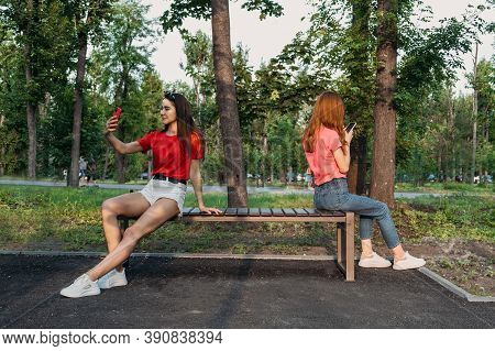 Social Distancing, New Normal Concept. Two Woman Girlfriends With Cell Phone Sitting On Bench In Par