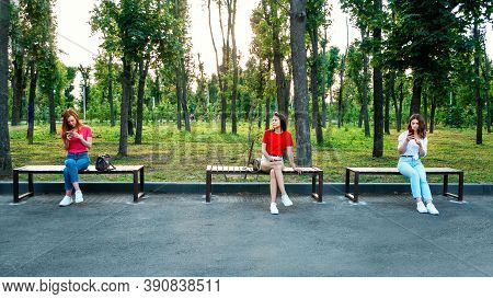 Social Distancing, New Normal Concept. Three Woman Girlfriends With Cell Phone Sitting On Bench In P