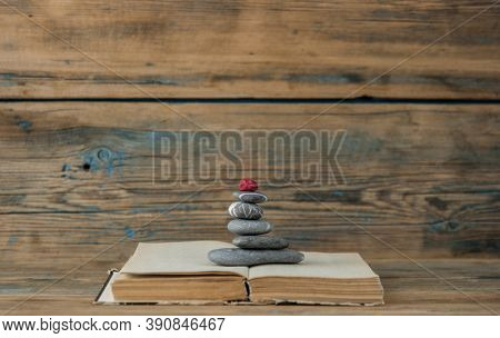 books and stack of zen stones on wood table background. Feng Shui, Balance and relaxation concept.