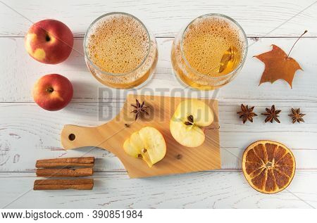 Ripe Fresh Juicy Red Apples, And Glasses With Cider On A Light Wooden Surface. Horizontal Orientatio