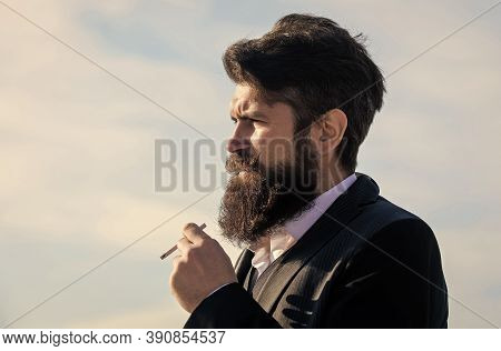 Man With Beard And Mustache Hold Cigarette. Bearded Hipster Smoking Cigarette Blue Sky Background. G