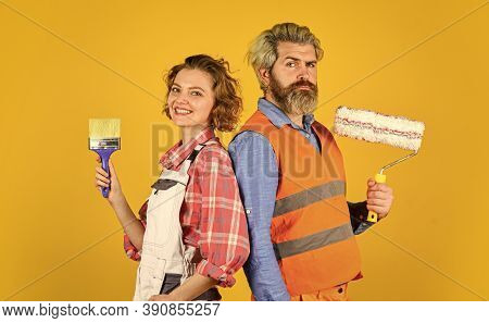 Doing Apartment Repair Together Themselves. Man And Woman Use Paint Brush And Roller. Couple At The
