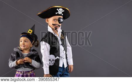 Happy Kids, Pirate Boy And Little Witch For Halloween. Children In Carnival Costumes On A Gray Backg