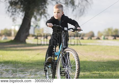 The Six Years Old Blond Hair Boy In Black Is Sitting On His Bicycle Outdoors.