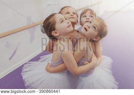 Adorable Little Girls In Leotards And Tutu Skirts Embracing, Looking Away Joyfully. Group Of Cute Yo