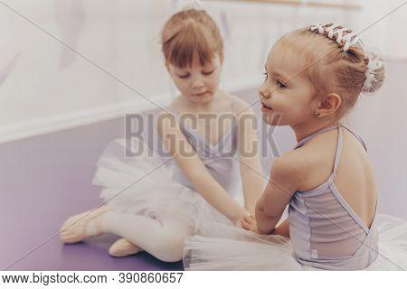 Lovely Little Girl Sitting On The Floor With Her Best Friend At Ballet School. Cute Little Ballerina