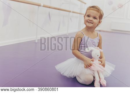 Charming Little Ballerina Sitting On The Floor With Her Rabbit Toy, Smiling Joyfully Looking Away, C