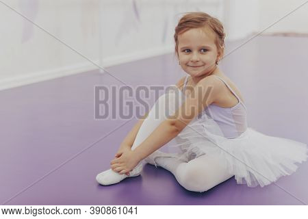 Cute Little Happy Ballerina Smiling To The Camera Sitting On The Floor At Ballet School. Adorable Li