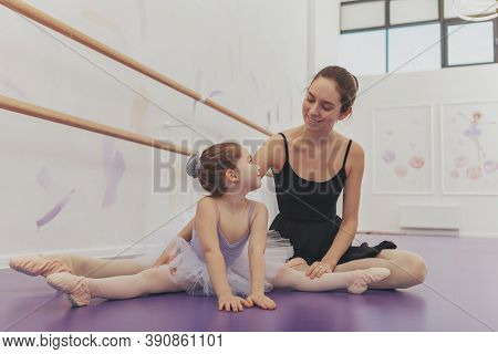 Adorable Little Girl In Tutu And Leotard Smiling Joyfully At Her Ballet Teacher, While Stretching To