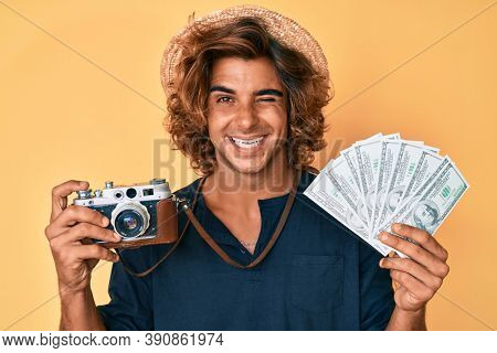 Young hispanic man holding vintage camera and dollars winking looking at the camera with sexy expression, cheerful and happy face.