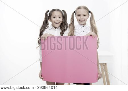Schoolgirls Hold Advertisement Poster Copy Space. Children Hold Advertising Banner. Happy Pupils Chi