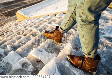 Winter Is Coming. Female Boots On Rough Slipper Ice Surface. A Woman In Brown Leather Shoes Descends