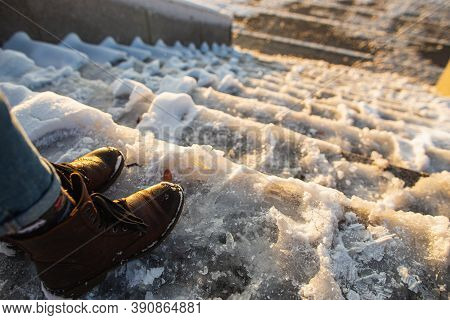 Danger Of Slipping. Female Boots On Rough Slipper Ice Surface. A Woman In Brown Leather Shoes Descen