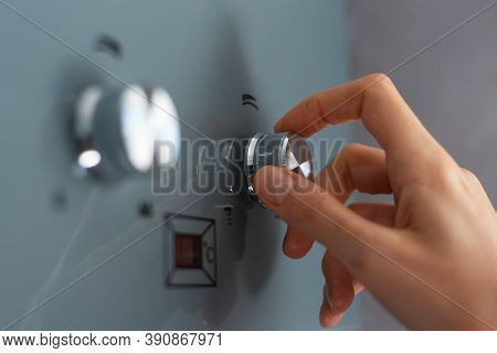 Close-up Of Female Hand Adjusting Temperature Of Water Heater. Modern Home Gas Fired Boiler.