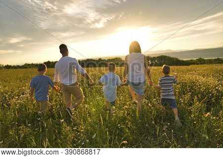 Happy Family On Daisy Field At The Sunset Having Great Time Together Walking Field