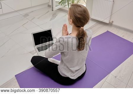 Back View Of A Blonde Woman In The Lotus Position, Looking At The Laptop Screen.