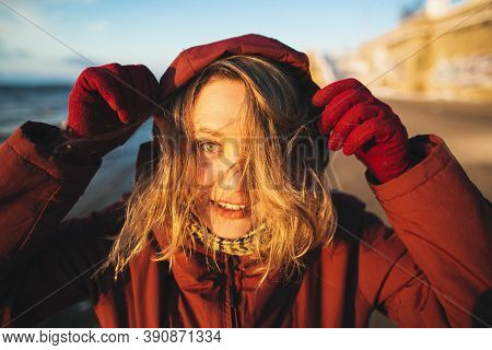 Beautiful Girl With Wild Hair Pulls The Hood Over Her Head. Sunny Winter Day On The Beach