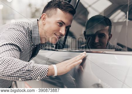 Close Up Shot Of A Handsome Happy Man Touching New Car At The Dealership Gently. Attractive Male Cus
