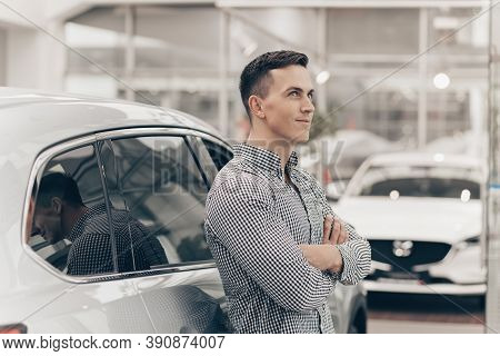 Handsome Man Leaning On A New Car At The Dealership, Looking Away Thoughtfully, Copy Space. Attracti