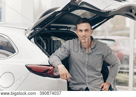 Handsome Cheerful Man Sitting In An Open Trunk Of His Newly Bought Car. Happy Male Driver Posing Wit