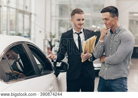 Professional Car Dealer Showing Cars On Sale To His Male Customer, Working At The Auto Dealership Sa
