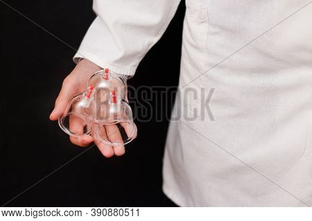 Jars For Hijama Bloodletting In The Hands Of A Doctor In A White Coat On A Black Background. Hijama