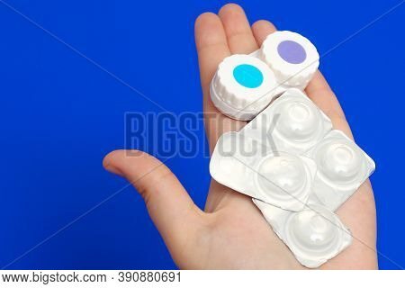 A Container For Contact Lenses And Lenses On The Hands Of A Woman On A Blue Background