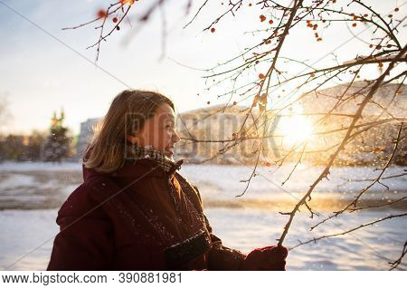 Winter Seasonal Activities. Beautiful Woman Throwing Snow In The Air At Sunset In Holding Tree Branc