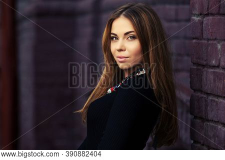 Young woman walking on city street Stylish fashion model with long straight hair in black sweater dress