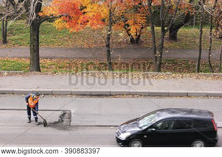 Russia, Vladivostok October 21, 2020: Road Worker And Car On The Road. A Road Worker In An Orange Ve