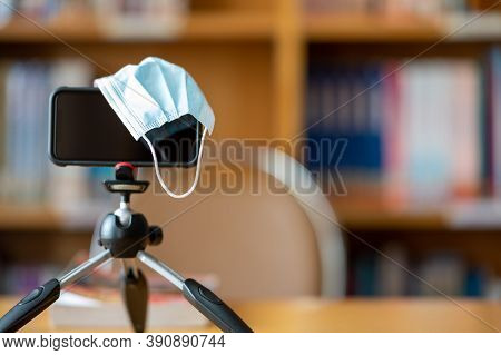 A Medical Mask And A Mobile Phone Mounted On A Tripod Are Used To Teach Students Online At The Libra