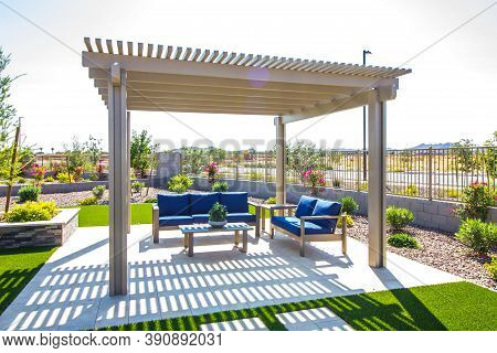 Rear Yard Pergola Covering Coffee Table & Two Couches With Blue Cushions